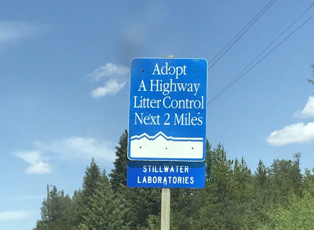 "Highway sign. ""Adopt A Highway Litter Control Next 2 Miles. STILLWATER LABORATORIES"""